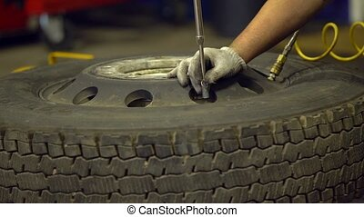 Repairing wheel by a mechanic. Old wheel repearing -...