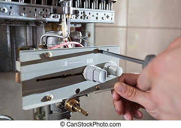 Repairman adjusting gas water heater - Plumber fixing a gas...