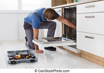 Repairman Examining Dishwasher In Kitchen