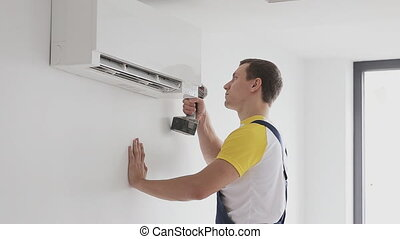 Repairman fixing air conditioning indoor - air conditioning...