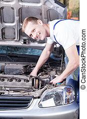 Repairman fixing car engine