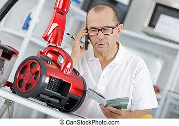 repairman fixing vacuum cleaner