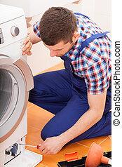 Repairman fixing washing machine