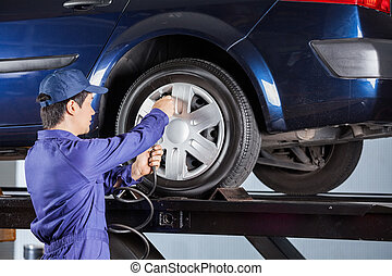 Repairman Inflating Tire Of Lifted Car - Young male...