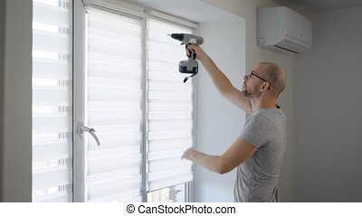 Repairman installing new striped blinds on a window in flat using drill.