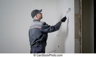 Repairman is decorating the room in the flat. - Qualified...