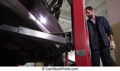 Repairman lowering car on lift after inspection - Automobile...