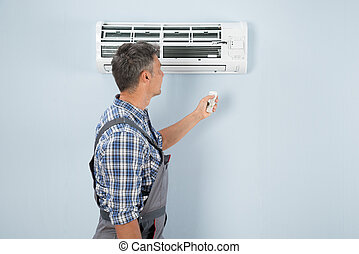 Repairman Operating Air Conditioner With Remote Controller