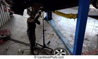 repairman repairing brake system on lifted up sedan car in car repair shop