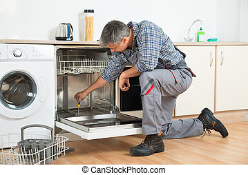 Repairman Repairing Dishwasher With Screwdriver In Kitchen