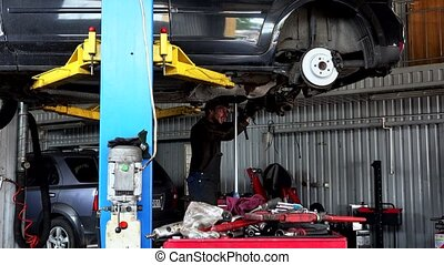 repairman repairing exhaust system on lifted up sedan car in car repair shop