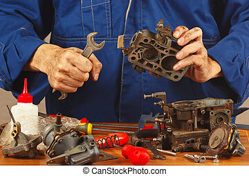 Repairman repairing parts of the old automobile engine in...