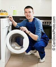 Repairman repairing washing machine at home