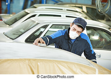 repairman sanding automobile roof