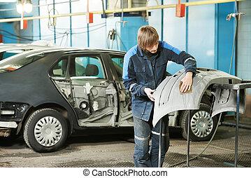 professional repairman worker in automotive industry sanding plastic body car bumper