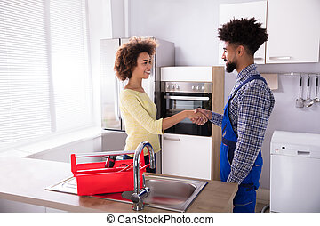 Repairman Shaking Hands With Young Woman