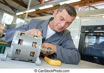 Repairman testing cylindrical component with multimeter