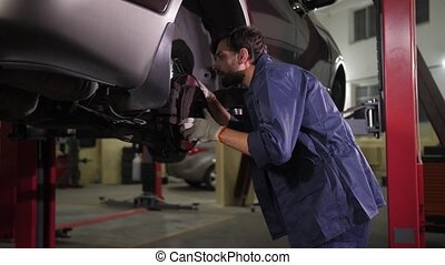 Auto repair specialist checking chassis of lifted car with wheel removed during vehicle maintenance. Automobile mechanic highlighting underbody during inspection of running gear in car repair service