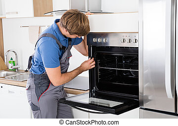 Repairman With Screwdriver Fixing Oven