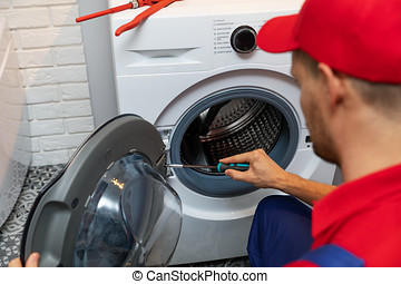 repairman with screwdriver repairing washing machine door