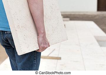 Repairman with slab - Closeup of repairman carrying concrete...