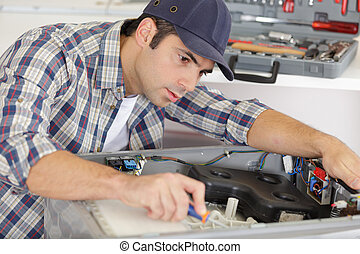 repairman working on a washing machine