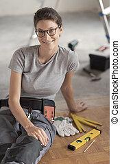 Repairwoman sitting on the floor and posing