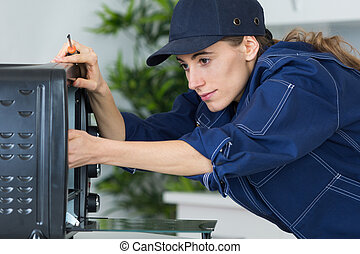 repairwoman with screwdriver fixing oven in kitchen