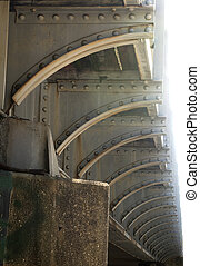 Repeating arcs of rivets support underside of railroad...