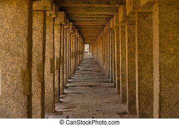 Stone columns repeat down a long covered walkway in the ancient ruins of Hampi, Karnataka, India