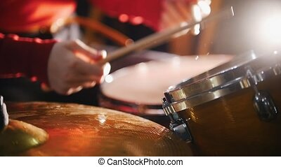 Repetition. Girl actively playing on wet drums.