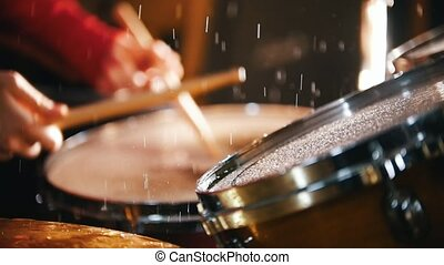 Repetition. Girl actively playing on wet drums. Water splash
