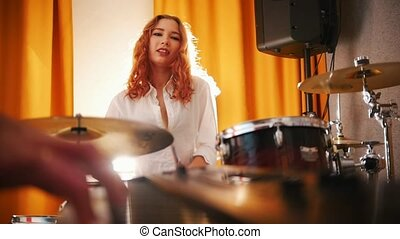Repetition. Girl drummer and a guy on keyboards. Focus from drums to hands