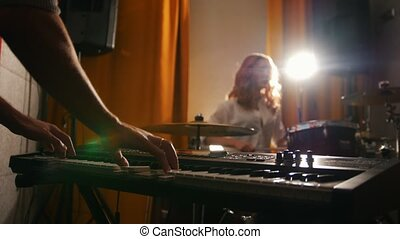 Repetition. Girl drummer and a guy on keyboards. Hands in focus
