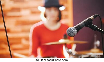 Repetition. Girl drummer concentratedly playing drums in studio. Mic in focus
