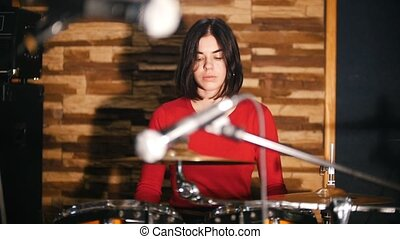 Repetition. Girl enthusiastically plays the drums
