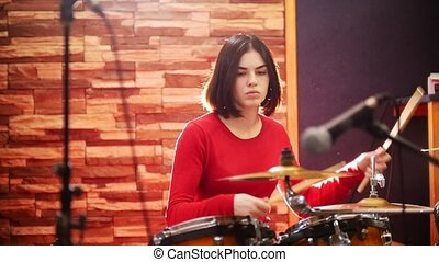 Repetition. Girl in red sweater fervently plays the drums in a studio.