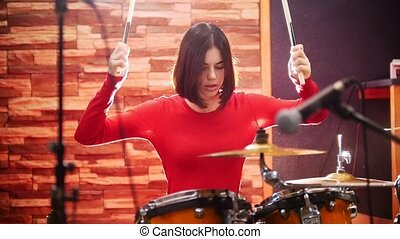Repetition. Girl in red sweater passionately plays the drums in a studio.