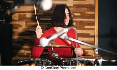 Repetition. Girl passionately plays the drums