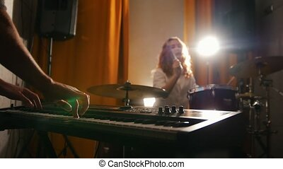 Repetition. Girl playing drums and a guy on keyboards. Hands in focus