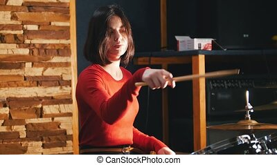 Repetition. Girl playing drums in studio