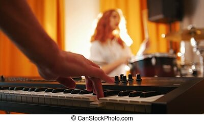 Repetition. Girl playing on drums and a guy on keyboards. Focus from hands to drums