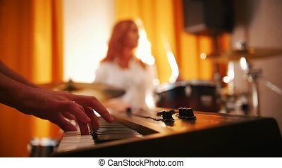 Repetition. Girl playing on drums and a guy on keyboards. Focus on hands. Backlight