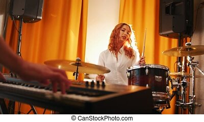 Repetition. Girl playing on drums and a guy on keyboards. Hands in focus. Slider shot