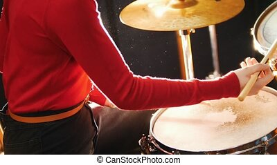 Repetition. Girl plays the drums. No face shown