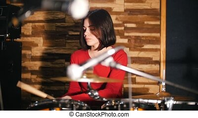Repetition. Pretty girl passionately plays the drums
