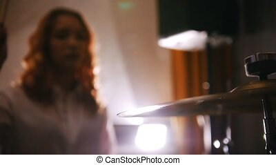 Repetition. Redhead girl plays on drums. makes and stops...