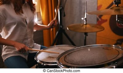 Repetition. Redhead girl plays on drums. Studiolights. Focus...