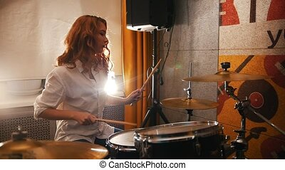 Repetition. Redhead girl plays on drums. Studiolights...