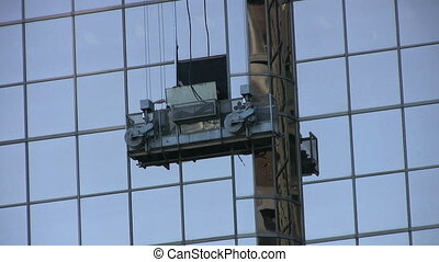 Replacing A High Rise Window - A pair of workers replace a...